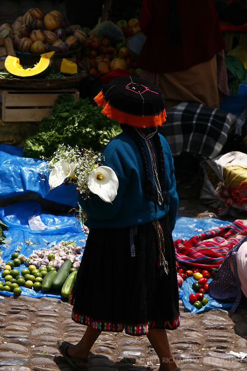 A Peruvian woman walks down the street in the Pisac market.