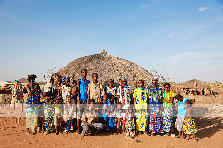 In the Fulani village of Jolooga in northern Burkina Faso, villagers stand outside a traditional house made from straw.