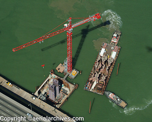 aerial photograph of one of the construction cranes and a barge being held in place by two tug boats during the construction of the San Francisco Oakland Bay Bridge