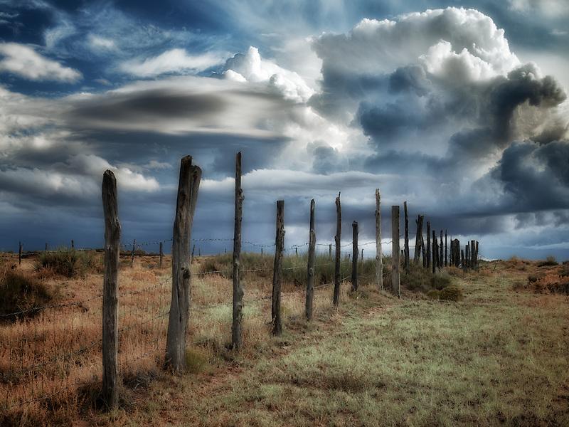 Fence line and thunderstorm clouds near Coal Mine Canyon, Arizona
