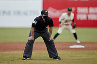 Umpire Greg Roemer handles the calls on the bases during the minor league baseball game between the Rome Braves and the Greensboro Grasshoppers at First National Bank Field on May 16, 2021 in Greensboro, North Carolina. (Brian Westerholt/Four Seam Images)