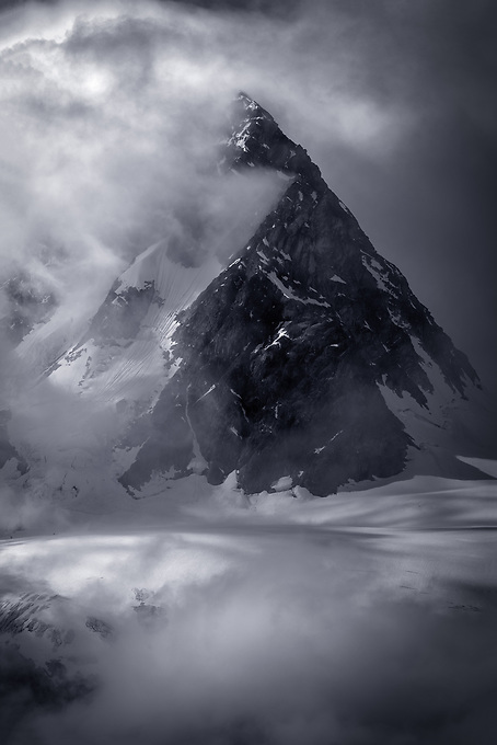 A mountain summit peaks through clouds and fog on the shoulder of an incoming storm.