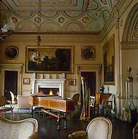 The music room at Nostell Priory is furnished formally with Louis XVI armchairs and canapes and has a spectacular painted plasterwork ceiling