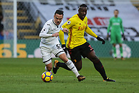 (L-R) Roque Mesa of Swansea City closely marked by Stefano Okaka of Watford during the Premier League match between Watford and Swansea City at the Vicarage Road, Watford, England, UK. Saturday 30 December 2017