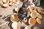 A boy in the Fulani village of Senosa, near Djenne, Mali, stands in a sea of calabashes.  The calabashes are made from gourd plants and will be sold in market.
