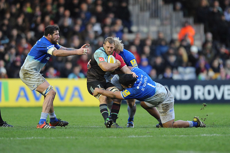 Chris Robshaw of Harlequins is tackled by Jim Hamilton, Petrus du Plessis and Mako Vunipola of Saracens during the Premiership Rugby match between Harlequins and Saracens - 09/01/2016 - Twickenham Stoop, London<br /> Mandatory Credit: Rob Munro/Stewart Communications
