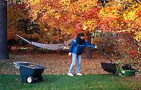 Woman cutting the lawn in autumn.