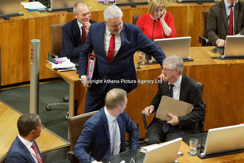 Pictured: First Minister for Wales Carwyn Jones (C) touches his successor Mark Drakeford as he walks out of the Senedd. Tuesday 11 December 2018<br /> Re: First Minister for Wales Carwyn Jones during his last First Minister Questions at the Senedd in Cardiff Bay, Wales, UK. He will be succeeded by Assembly Member Mark Drakeford.