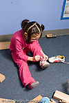 Education Preschool 3-4 year olds skills girl tying own shoe sitting in doll cradle wearing glasses vertical