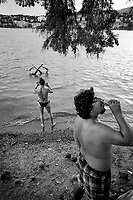 Switzerland. Canton Ticino. Lugano. Ciani Park. Hot summer day. A man is drinking a cold beer while a mother takes pictures of her daughters making with their feet synchronized swimming figures in the water . Synchronised swimming or artistic swimming is a hybrid form of swimming, dance, and gymnastics, consisting of swimmers performing a synchronised routine (either solo, duet, trio, mixed duet, free team, free combination, and highlight) of elaborate moves in the water. Parco Ciani is a green area on the lake near the town center. Built in 1845, when the Ciani brothers purchased the property, it became in 1912 the property of Lugano municipality. It covers an area of about 63,000 (sq m). 2.08.2020 © 2020 Didier Ruef