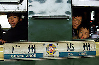 Passengers  look out from the windows of a train from Dazhou, Sichuan province to Guangzhou at the railway station of Dazhou, Sichuan province, China..22-OCT-03