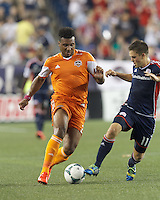 Houston Dynamo midfielder Giles Barnes (23) on the attack as New England Revolution midfielder Kelyn Rowe (11) defends. In a Major League Soccer (MLS) match, Houston Dynamo (orange) defeated the New England Revolution (blue), 2-1, at Gillette Stadium on July 13, 2013.