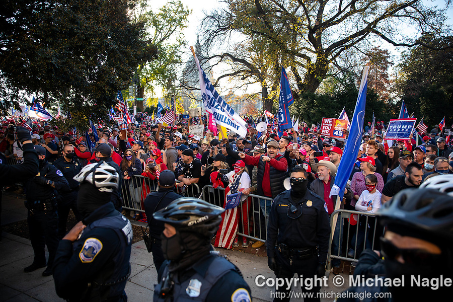 """Trump supporters scream at anti-Trump protesters during the """"Million MAGA March"""" on November 14, 2020 in Washington, D.C.  Thousands of supporters of U.S. President Donald Trump gathered to protest the results of the 2020 presidential election won by President-Elect Joe Biden.  Photograph by Michael Nagle"""