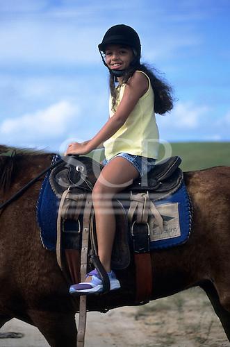Sauipe, Bahia State, Brazil. Smiling girl tourist on horseback.