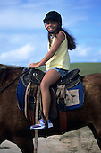 Sauipe, Bahia State, Brazil. Smiling girl tourist on horseback.