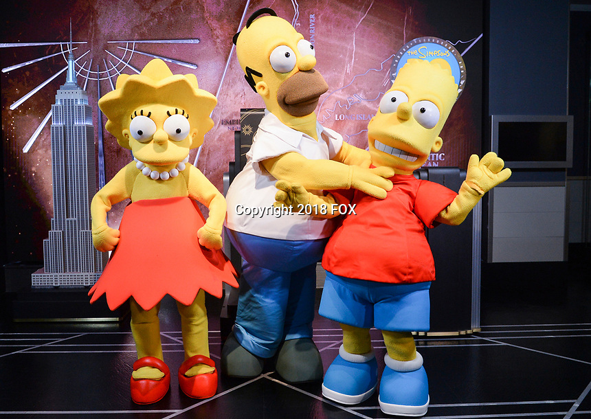 """New York - DECEMBER 17: Simpsons Costumed characters, participate in the ceremonial lighting of the Empire State Building as they attend the Empire State Building Celebration of the 30th Anniversary of FOX's """"The Simpsons"""" on December 17, 2018 in New York City.  (Photo by Anthony Behar/FOX/PictureGroup)"""