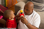 Father demonsrates jack-in-the-box toy to 12 month old baby son