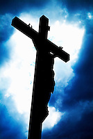 Silhouetted crucifix against a cloudy sky.