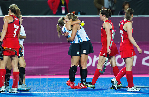 08 AUG 2012 - LONDON, GBR - Macarena Rodriguez-Perez (centre left) and Daniela Sruoga (ARG) (centre right) both of Argentian celebrate their victory over Great Britain in their London 2012 Olympic Games semi final hockey match at the Riverbank Arena in Stratford, London, Great Britain (PHOTO (C) 2012 NIGEL FARROW)