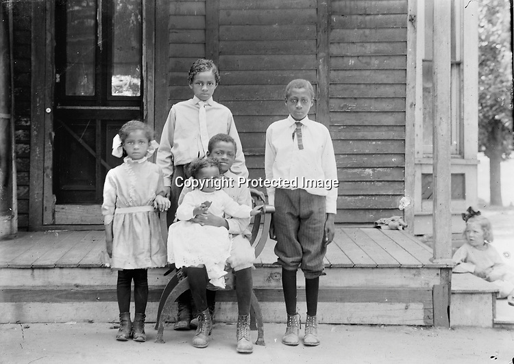Cora and Alonzo (Lon) Thomas operated a small grocery from the front room of this house at 715 C Street. Four of their five children are portrayed here. Baby Lonnie, born in 1909, sits on Herschel's lap. Agnes stands at left, and eldest son Wendell stands at the center. The young man at right is probably Lucius Knight, their mother's half brother. Wendell worked a typical variety of jobs in Lincoln--waiter, clerk, porter, laborer, and janitor--before founding the Thomas Funeral Home in Omaha. The Thomas family and many other African American families lived in the South Bottoms, a neighborhood mainly of Germans from Russia, Lincoln's largest immigrant group. The little blonde girl who leans into the right edge of this view serves as a reminder that Lincoln's residential neighborhoods were not segregated by race in the early 20th century--poor people of many ethnicities lived together. A few years later and through the middle third of that century, residential segregation became prevalent in Lincoln. A close-knit black neighborhood arose from that adversity, centered around Twenty-first and T Streets.<br /> <br /> INFORMATION SUBMITTED BY STAN SCHMUNK 2/22/2017 The little girl is Marie Busche, daughter of German immigrant Fred Busche. She's 3 years old in this photo. By 1930 she and her father are alone in the house at 703 C. Volga Germans later bought it and were living there when I was growing up. But now one of my high school classmates lives there with his wife!!<br /> <br /> More by Stan 8/1/2017: This house was built in 1886-1887 and stayed in the black community through the 1970s. It waas built for a veteran of the Civil War who became a coal miner in Virginia. He was disabled to some degree. He and his family only stayed in Lincoln for a short time before moving to Denver, possibly for his health. He passed away in the early 90s and his wife then took her brood to Los Angeles. She later passed and is buried in the old cemetery just north of the 10 in Los Angel