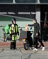 Nederland  Amsterdam  2020.   Oudere bezorger van Uber Eats levert een lunch af bij een kantoor.  Foto mag niet in negatieve / schadelijke context worden gepubliceerd.   Foto : ANP/ HH / Berlinda van Dam