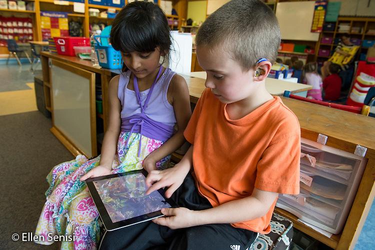 MR / Schenectady, NY. Zoller Elementary School (urban public school). Kindergarten inclusion classroom. Two students use iPad to read an educational eBook / app. Boy: 5, hearing impaired; Girl: 5, biracial  MR: Shu20, Myk1. ID: AM-gKw. © Ellen B. Senisi.