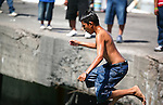 Young boy leaps from pier during Mexico's annual Navy Day celebration