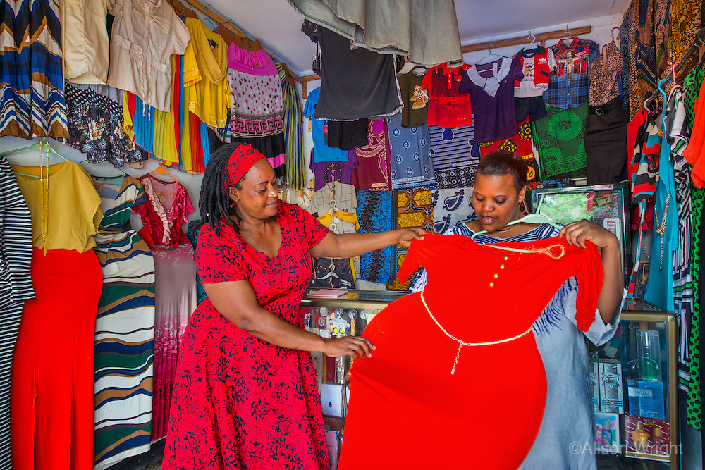 AWright_Tanz_008233.jpg<br /> Tanzania<br /> Flora Edward (left) lives in Morogoro, where she has managed a dress shop for the last nine years. Flora receives loans from BRAC's microfinance program, which has helped her expand the business. Here, she sizes a dress for one of her customers.