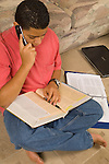 15 year old teenage boy at home doing homework and talking on cell telephone vertical Hispanic Puerto Rican