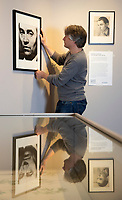 BNPS.co.uk (01202) 558833. <br /> Pic: CorinMesser/BNPS<br /> <br /> Pictured: Museum Director Adrian Green hangs a portrait of Richard Chopping in the exhibition.<br /> <br /> Original artwork from the acclaimed James Bond illustrator has gone on display at a new exhibition.<br /> <br /> Richard Chopping produced the drawings for nine of the 007 book covers from 1957 to 1966.<br /> <br /> Examples of his craft, including his striking skull design for Goldfinger, are being showcased at Salisbury Museum in Wiltshire.