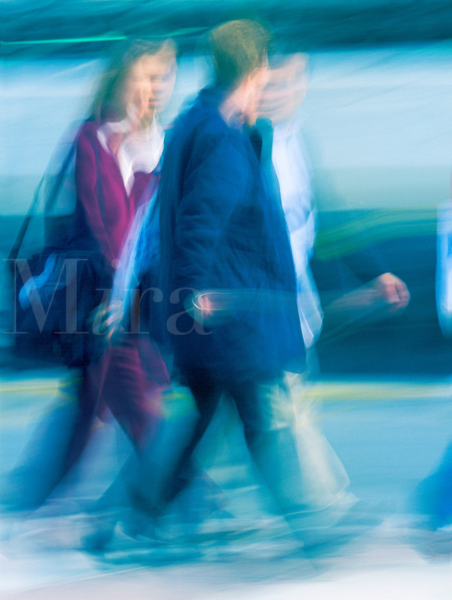 Blurred shot of business men and woman walking in a busy downtown setting