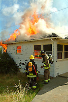 Firefighters from the Occidental Volunteer Fire Department fight a structure fire during a training exercise in which a house is burned to the ground. Occidental, California.