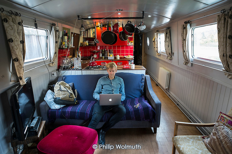 Chouf in his widebeam narrowboat at newly-built permanent moorings on the Grand Union canal in Hackney, London.
