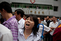 A Han Chinese woman shouts at police who arrested two Han men who were part of a mob that chased down a Uighur in Urumqi. They caught up with the Uighur and beat him before the police intervened firing shots in the air and arresting the two Han attackers. The mob then attacked the police to try and stop the arrests. Ethnic violence between the Uighur and Han people had erupted in the city a few days earlier.