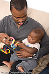 5 mopnth old baby boy held by father interested in toy vertical African American