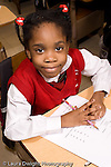 K-8 Parochial School Bronx New York Grade 1 portrait of girl with language arts worksheet on desk in front of her vertical