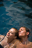 Young ouple floating in water, elevated view