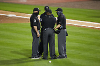 The umpiring crew huddles together to discuss a call during the NCAA baseball game between the North Carolina Tar Heels and the South Carolina Gamecocks at Truist Field on April 6, 2021 in Charlotte, North Carolina. (Brian Westerholt/Four Seam Images)