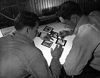 Students of Class II Advanced Ground Photography learn to make lantern slides.  A student submits his slides to Instructor M. Deskovitch, PhoM 1/c on the right.