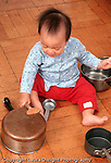 10 month old baby girl sitting full length playing with pots and pans hitting pan with wooden spoon Asian Vietnamese vertical
