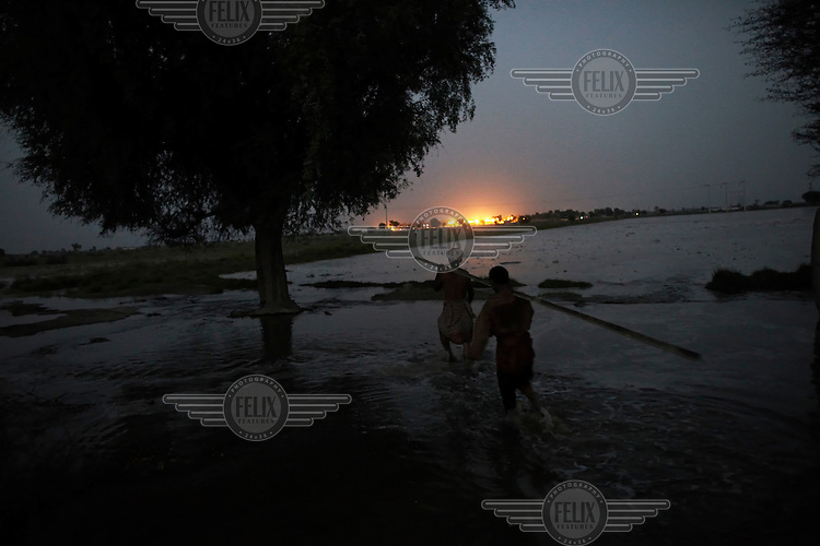 Men try to salvage what they can by storing possessions in trees beside their home as flood water inundates the surrounding area after Manchar Lake bursts its banks, near Bubak, Sindh province, Pakistan.