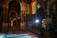 """Gianni Crea, the Vatican Museums chief """"Clavigero"""" key-keeper, holds a torch and a bunch of keys as he walks to open the museum's rooms and sections, at the Vatican, Monday, Feb. 1, 2021. Crea is the """"clavigero"""" of the Vatican Museums, the chief key-keeper whose job begins each morning at 5 a.m., opening the doors and turning on the lights through 7 kilometers of one of the world's greatest collections of art and antiquities. The Associated Press followed Crea on his rounds the first day the museum reopened to the public, joining him in the underground """"bunker"""" where the 2,797 keys to the Vatican treasures are kept in wall safes overnight. (AP Photo/Andrew Medichini)"""