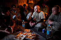 US Army Soldiers from Viper Company 126, 1st Platoon eat dinner and discuss projects with their Afghan contractors at Restrepo Firebase in the restive Korengal Valley. Restrepo, a remote outpost, is known as one of the most violent places in Afghanistan. Located in the Korengal Valley it comes under fire on a daily basis from Anti-Afghan Forces in the local villages and mountains.