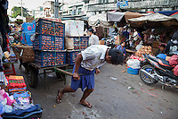 Myanmar, Burma.  Mandalay Market Scene.  Man Struggles to Pull a Load of Apples and Oranges through the Market Streets.