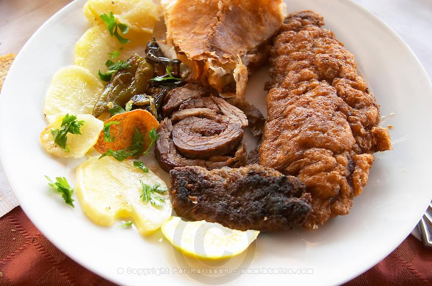 Traditional dish with potatoes, rolled roast lamb, fried fish, kafta meat balls. Berat lower town. Albania, Balkan, Europe.