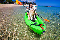 A young Asian woman kayaking in Mokuleia with her Golden Retriever dog