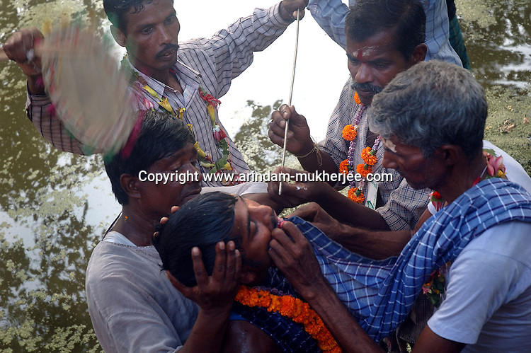 On the eve of Bengali new year an Indian man piercing his tounge with an iron rod to bring good fate in the new yearwhile viewers watch the cerimoney. This is a sacrifice to Lord Siva done by people staying in the rural Bengal. Another form of religious blindness in one of the fastest developing country. Medinipore near Kolkata, India. Arindam Mukherjee
