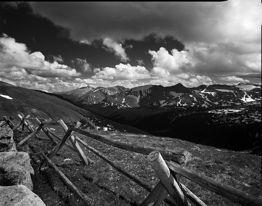 """""""Alpine Fence""""<br /> Rocky Mountain National Park, Colorado<br />  2011<br /> <br /> A rustic fence forms a border between the breathless landscape and Trail Ridge Road in Rocky Mountain National Park.  The scenic outlook captured the grazing lands of elk, while the scattering of clouds softened the ruggedness of the distant peaks.  The 48-mile scenic drive along this road allows the traveler to stop and admire the vistas. <br /> <br /> 4 x 5 Large Format Film"""