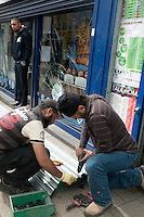 Two men prepare to board up the damaged O2 mobile shop on Mare Street in the London borough of Hackney. London saw the beginnings of riots on Saturday evening, after a peaceful protest in response to the shooting by police of Mark Duggan during an attempted arrest, escalated into violence. By the third night of violence, rioting had spread to many areas of the capital and to other cities around the country.