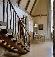 A staircase of rough-hewn logs on one side of this double height pine-clad living room with a Swedish-style dining table and chairs in one corner